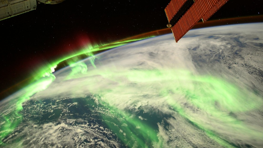 The astronaut shows a glowing photo taken from space of the aurora glowing green and red above the earth