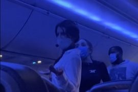 """The woman was stopped on the plane while using a microphone to explain Kovid's """"true origin."""""""